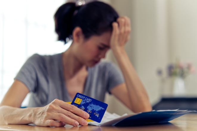 Stressed young sitting Asian woman hands holding credit card and bills worry about find money to pay credit card debt and all loan bills. She is putting hand on her head. Financial problem concept.